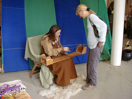 Seagyth demonstrating her tablet weaving.