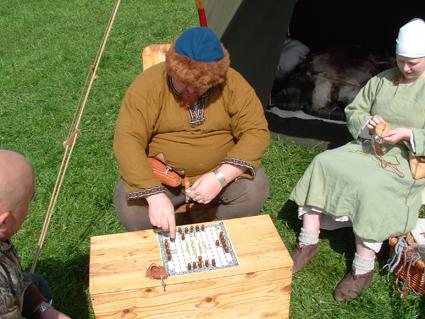 Demonstrating a game of hnefatafl.